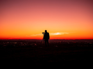 Image of a silhouette of a man with tripot and camera standing on a hill during colorful sunset