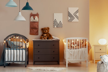 Warm baby bedroom interior with white and grey cribs, commode and small nightstand table with lamp