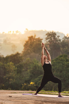 Portrait of young female practicing yoga in warrior posture. with the nature during sunrise in the morning. Peaceful, mindfulness and Healthcare concept.