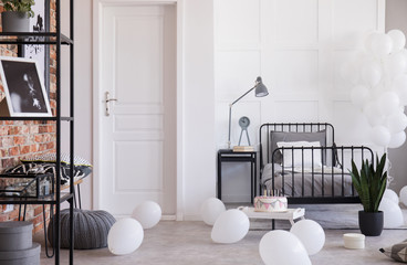 Grey lamp and clock on nightstand next to single metal bed in industrial bedroom with balloons