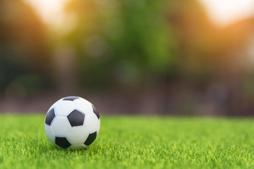 Soccer ball on grass green field with copy space