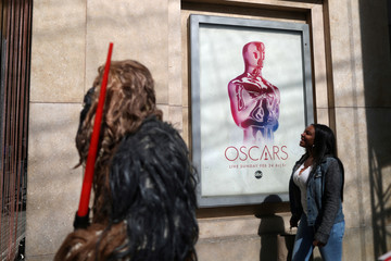 People walk past an Oscars sign as preparations continue for the 91st Academy Awards in Hollywood, Los Angeles
