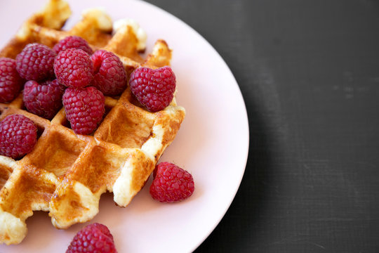 Traditional belgian waffle with raspberries on pink plate over black background, side view. Copy space.