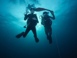 Young woman and man scuba divers exploring