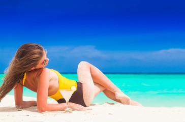 Fit woman in sun hat and bikini at beach