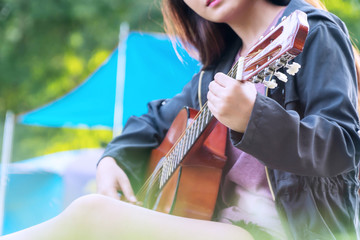 Travel alone young woman playing acoustic guitar at camping. Girl playing guitar in her free time hand focus.