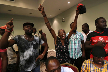 Supporters react as members of 'Democratic and Popular Sector' political coalition deliver a speech during a news conference in Port-au-Prince