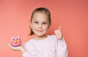 girl with a piggy bank on a pink background