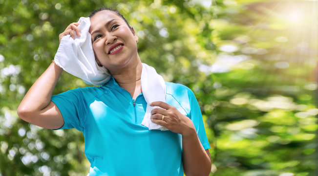 Elderly lifestyle concept. Attractive senior women 50s smiling while wiping her throat with white towel on neck after exercises in the public park.