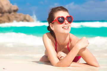 portrait of pretty woman in heart shaped sunglasses relaxing at tropical beach. La Digue, Seychelles