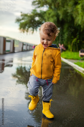 f1ac1d87a97d65 Child in a yellow waterproof coat in the rain jumping in puddles. A boy  stands with his head bowed in rain, a bright raincoat. Kid playing autumn  park.