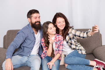 Capture happy moments. Family selfie. Family spend weekend together. Use smartphone for selfie. Friendly family having fun together. Mom dad and daughter relaxing on couch. Family posing for photo