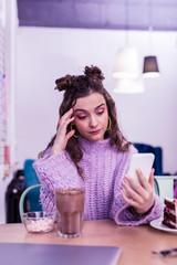 Skeptical long-haired girl in knitted sweater checking social medias