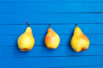 Pear decoration stock images. Yellow pear on blue background. Pear home decor. Yellow decorative pear