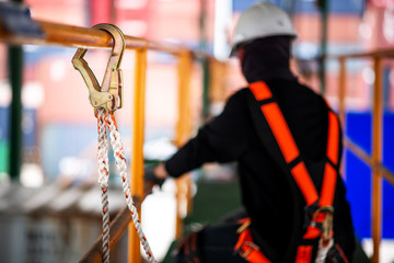 Construction worker wearing safety harness and safety line working on construction.