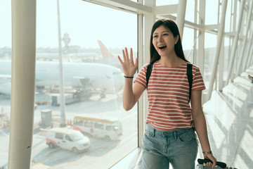 Girl waves her hand on arrival at airport