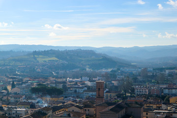 aerial view of the tuscany city Certaldo in morning winter fog with hills on the background, Italy