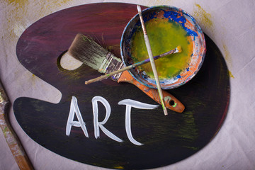 Overview of artist workstaion paintbrushes art painted on wooden painters mixing palette