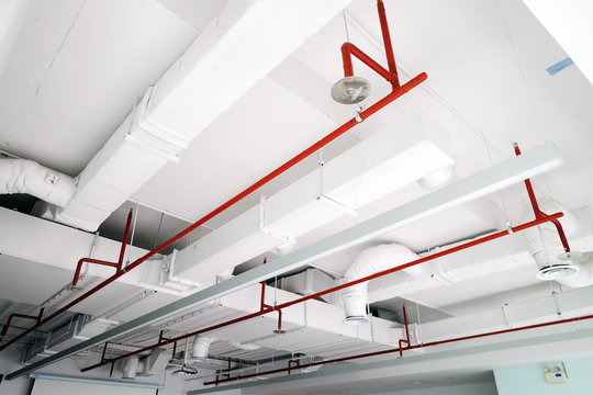 Perspective view of white air duct on the ceiling with red water sprinkler pipe