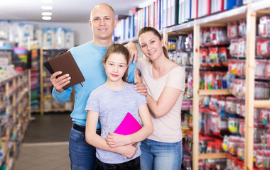 parents with daughter buying school supplies