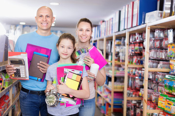 Family with daughter schoolgirl holding school accessories in store