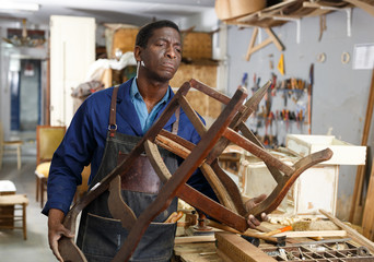 Craftsman restoring old chair in studio