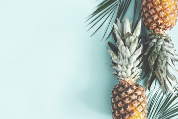Summer composition. Pineapple, palm leaves on pastel blue background. Summer concept. Flat lay, top view, copy space