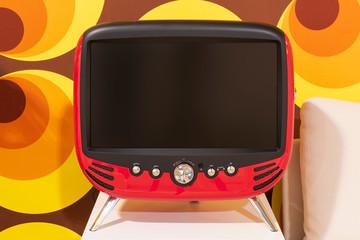 Roter retro Fernseher mit schwarzem Monitor und silbernen Knöpfen vor 70ér Jahre Tapete