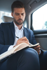 Businessman sitting in car and writing daily plan in his diary