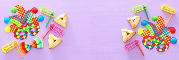 Purim celebration concept (jewish carnival holiday) with colorful joker or clown mask over wooden purple background. Banner.