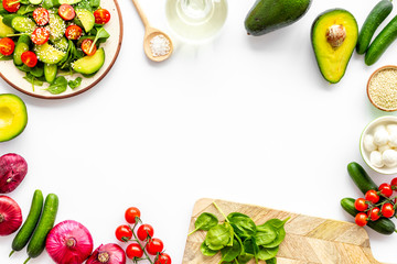 Preparing fresh salad. Vegetables, greens, spices on white background top view copy space frame Wall mural