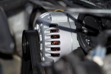 Ein Motor von einem Auto und Nahaufnahme der Lichtmaschine und Keilriemen
