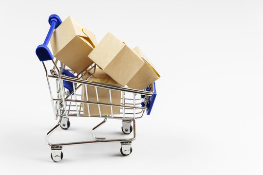 Supermarket cart with boxes on white background. The concept of delivery of goods, online shopping.
