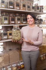 woman buyer selects herbs in store of ecological products