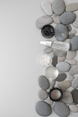 Natural organic cosmetics in pebble on grey background