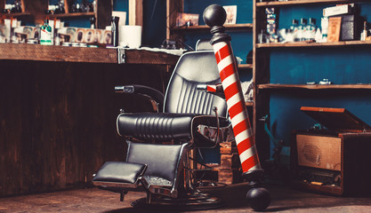 Barber shop pole. Logo of the barbershop, symbol. Stylish vintage barber chair. Hairstylist in barbershop interior. Barber shop chair. Barbershop armchair, hairdresser, hair salon, barber shop for men