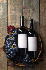 Grapes and bottles of red wine.