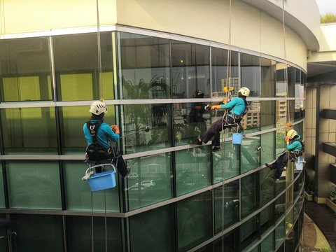 Rope access cleaning worker wearing safety harness hard hat working at height descending on rope performing washes a hospital complex glass wall.