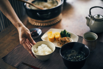 土鍋で炊いたご飯を茶碗によそう女性