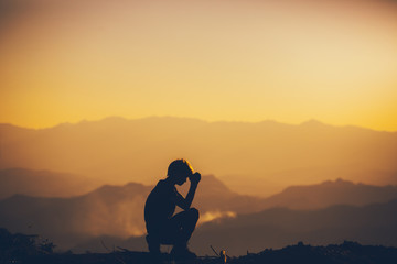 Man sitting praying and worshipping God at sunset background. christian silhouette concept.