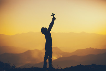 Young man standing holding christian cross for worshipping God at sunset background. christian silhouette concept.