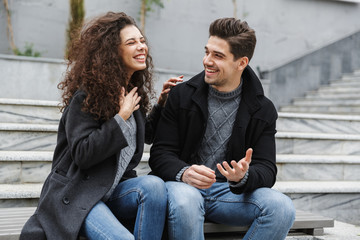 Image of joyful couple man and woman 20s in warm clothes, laughing while sitting on stairs outdoor