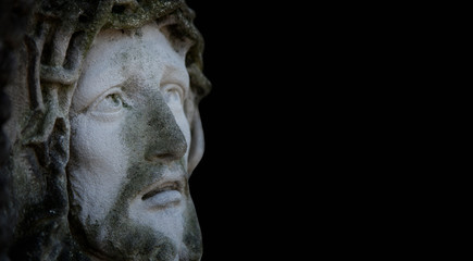 Fotomurales - Ancient statue of the crucifixion of Jesus Christ in profile agaist black background.