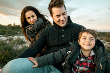 Portrait of a family smiling and happy in the countryside. Marriage with one child in the field