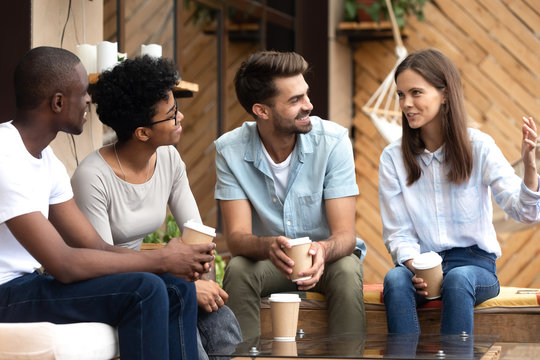 Friend listening to girl sitting together in cafe drinking coffee