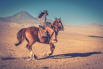 cowgirl woman riding a horse in the desert