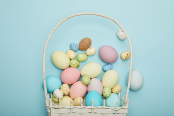 Top view of painted easter chicken and quail eggs in straw basket