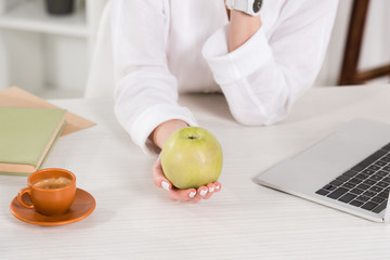 cropped view of woman holding green apple near laptop and cup in office