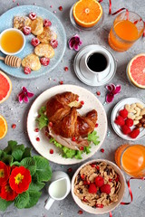 Breakfast food table. Festive brunch set, meal variety with pancakes, croissant, juice, fresh berries, granola and fresh fruits. Easter breakfast. Top view with copy space.