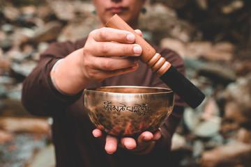 woman holding and playing a singing bowl tibetan bowl
